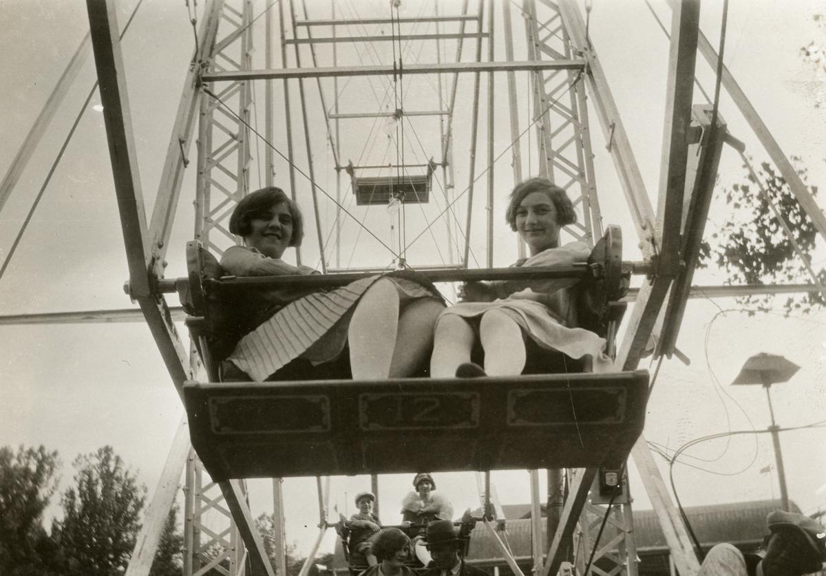 Low-angle portrait of a pair of young women as ride the Ferris wheel at the Coney Island amusement park, Cincinnati, Ohio, 1927