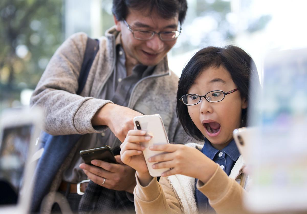 A girl reacts as she tries an iPhone X at the Apple Omotesando store on November 3, 2017 in Tokyo, Japan. Apple launched the latest iPhone featuring face recognition technology, a large 5.8-inch edge-to-edge high resolution OLED display and better front and back cameras with optical image stabilisation today