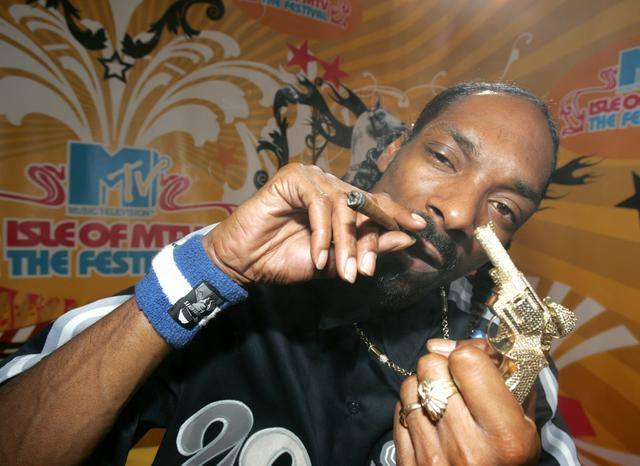 Snoop Dogg holds up a blunt and a gold gun