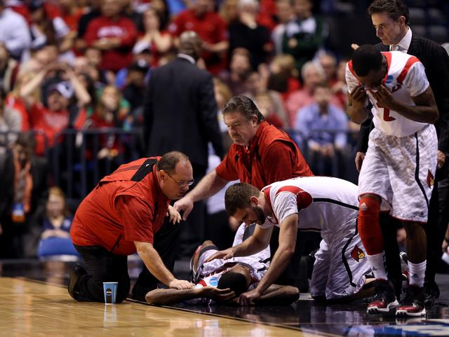 Kevin Ware #5 of the Louisville Cardinals talks with teammate Luke Hancock #11 as Ware is tended to by medical personnel after he injured his leg in the first half against the Duke Blue Devils during the Midwest Regional Final round of the 2013 NCAA Men's Basketball Tournament at Lucas Oil Stadium on March 31, 2013 in Indianapolis, Indiana