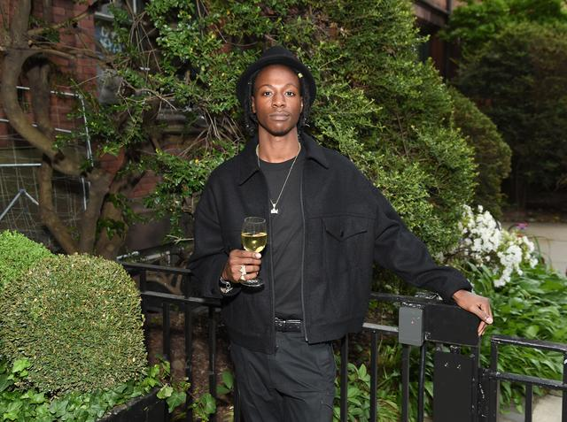 Joey Bada$$ with a glass of white wine