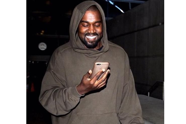 Kanye on the phone laughing at LAX