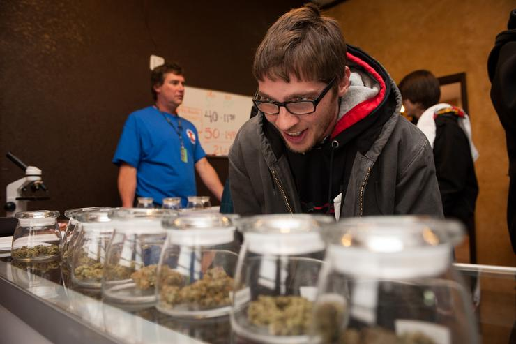 Tyler Williams of Blanchester, Ohio selects marijuana strains to purchase at the 3-D Denver Discrete Dispensary on January 1, 2014 in Denver, Colorado. Legalization of recreational marijuana sales in the state went into effect at 8am this morning.