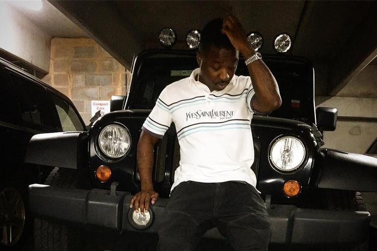 Troy Ave in front of his car