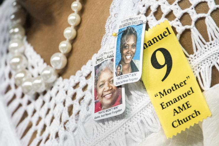 A woman wears tributes to Rev. Sharonda Singleton and Ethel Lance during a memorial service remembering the victims of the mass shooting at Emanuel African Methodist Episcopal (AME) Church June 17, 2016 in Charleston, South Carolina. Suspect Dylann Roof is charged with killing nine parishioners during a bible study session one year ago today at the historic Emanuel AME Church in Charleston.