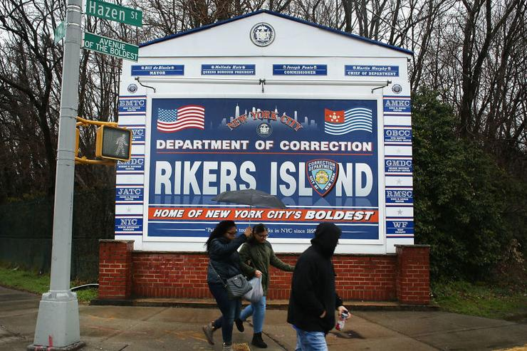 People walk by a sign at the entrance to Rikers Island on March 31, 2017 in New York City. New York Mayor Bill de Blasio has said that he agrees with the fundamentals of a plan to close the jail complex on Rikers Island within 10 years. A newly released report from an independent commission, led by Judge Jonathan Lippman and created by the City Council last year, has recommended the closer of the troubled facility.