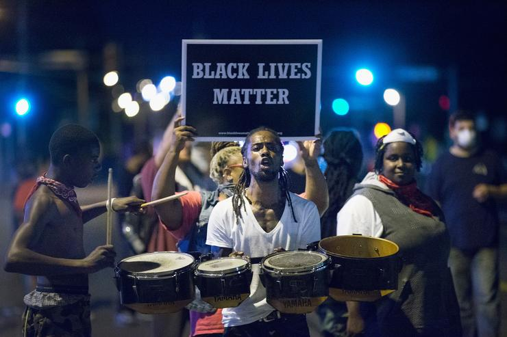 Demonstrators, marking the one-year anniversary of the shooting of Michael Brown, protest along West Florrisant Street on August 10, 2015 in Ferguson, Missouri