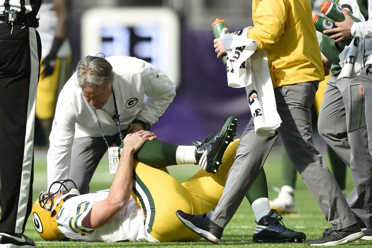 Aaron Rodgers #12 of the Green Bay Packers clenches his right knee after being hit during the first quarter of the game against the Minnesota Vikings on October 15, 2017