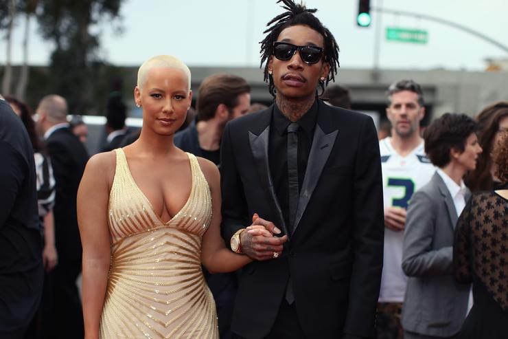 Recording artist Wiz Khalifa (R) featured wearing Converse in support of the GRAMMY Foundation's GRAMMY Camp and model Amber Rose attend the 56th GRAMMY Awards at Staples Center