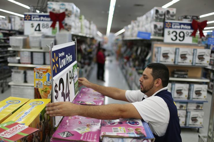 Jaime Vado fixes a display in the isle at a Walmart store as they prepare for Black Friday shoppers on November 24, 2015 in Miami, Florida. Black Friday, which is the day after Thanksgiving, is known as the first day of the Christmas shopping season and most retailers offer special deals on the day