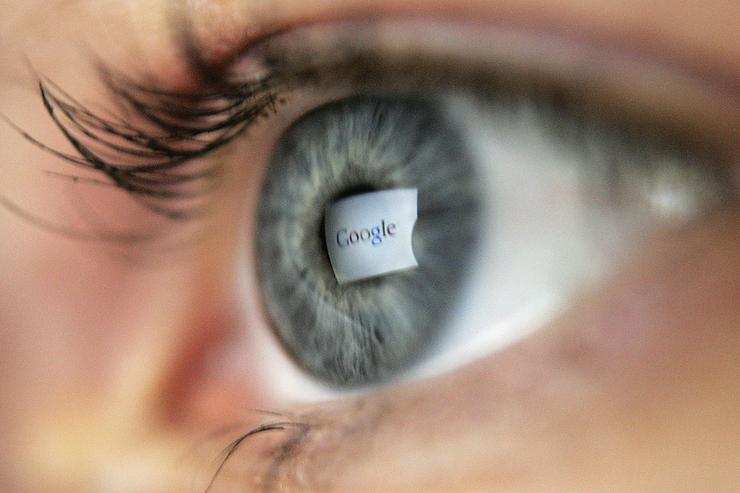 In this photo illustration, the logo of the multi-facetted internet giant Google is reflected in the eye of a woman looking at a computer screen, April 13, 2006 in London, England