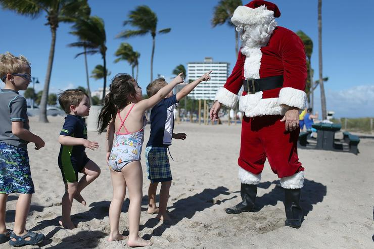 Timmy McGovern dressed as Santa Claus walks along the beach passing out candy canes and posing for pictures with beach goers on December 21, 2015 in Fort Lauderdale, Florida. Santa Claus has been visiting the beach just before Christmas for over 30 years