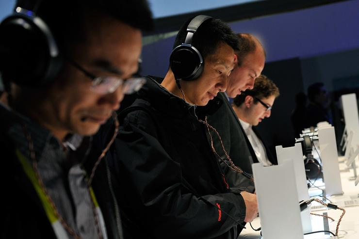 Attendees listen to music with Sony's MDR-1A headphones at the 2015 International CES at the Las Vegas Convention Center on January 6, 2015 in Las Vegas, Nevada. CES, the world's largest annual consumer technology trade show, runs through January 9 and is expected to feature 3,600 exhibitors showing off their latest products and services to about 150,000 attendees