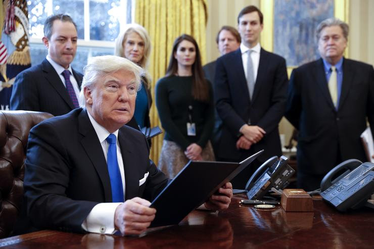 President Donald Trump signs one of five executive orders related to the oil pipeline industry in the Oval Office of the White House January 24, 2017 in Washington, DC. Looking on are White House Chief of Staff Reince Priebus, counselor to the President Kellyanne Conway, White House Communications Director Hope Hicks, Senior Advisor Jared Kushner (2nd R) and Senior Counselor Stephen Bannon (R)