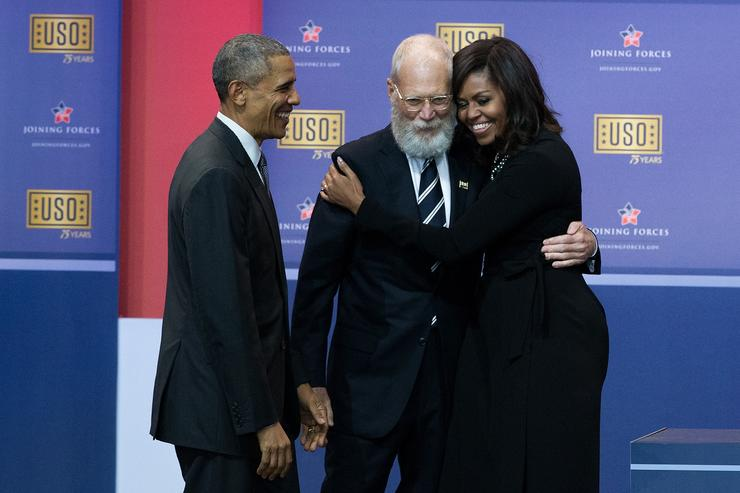 L to R, President Barack Obama looks on as David Letterman hugs First Lady Michelle Obama during a comedy show organized by United Services Organizations (USO) for members of the military and their families, at Andrews Air Force Base, May 5, 2016, in Joint Base Andrews, Maryland. The program is also being live streamed for active duty service members stationed at bases domestically and abroad.