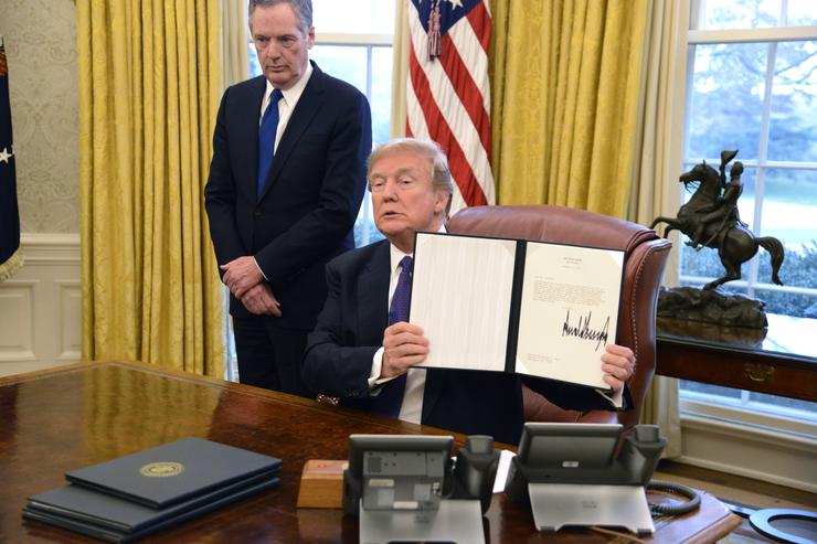 President Donald Trump displays a Section 201 action as US Trade Representative Robert Lighthizer witnesses, in the Oval Office, at the White House, January 23, 2018, in Washington, DC. The administration is issuing tariffs on imported solar panels and washing machines to protect American manufacturing companies against dumping by foreign countries, mainly China, and including South Korea